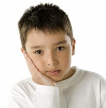 Boy with hand on face